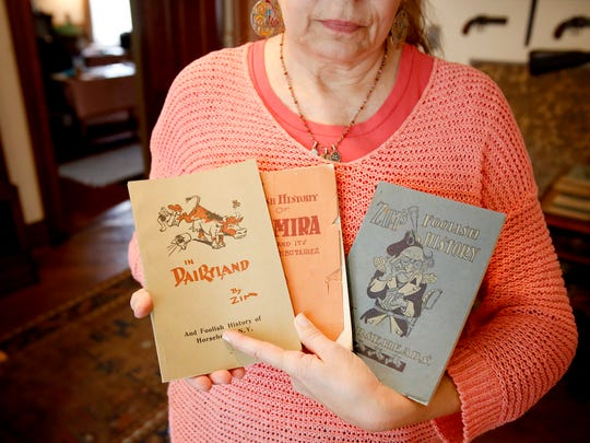 Cartoonist Eugene Zimmerman wrote and illustrated several books about the history and life in the local area. Marcia Tinker, board member for the Zim House museum, holds a few of them.
