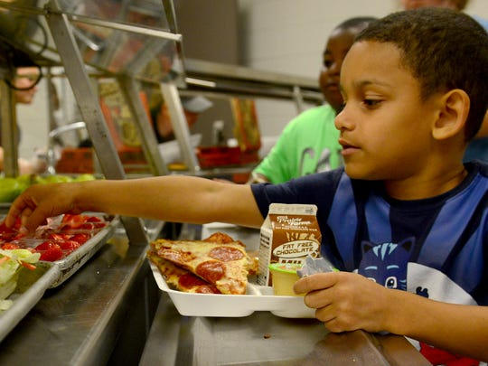 Bryson Buckley reaches for a bowl of fresh cut strawberries, Thursday, June 1, during the Seamless Summer Meals Program kickoff at Trenton Elementray School.