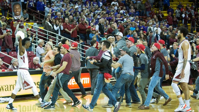 Aggie fans rush the court after the Aggies won 81-69 against Grand Canyon University, Thursday, January 12, 2017 at the Pan American Center.