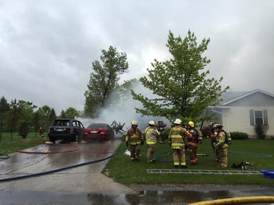 Two vehicles appear to have severe damage in the driveway of a home on fire on Breezewood Court in Plover.