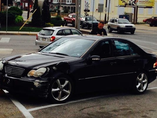 A York City Police officer examines the damage on a black Mercedes that allegedly struck a nearby garage.