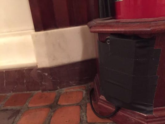 The camera of an iPhone taped to a fire extinguisher stand in the state Capitol is pointed toward Sen. Scott Wagner's office to keep on eye on his signs.