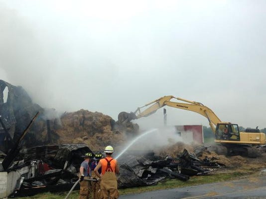 Crews called in a track hoe to pull the hay apart to extinguish any active fire.