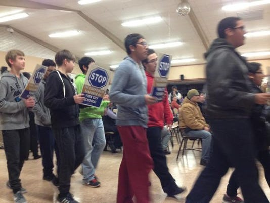"""York City School District students march before a school board meeting, saying """"Charters No. CRO must go."""""""