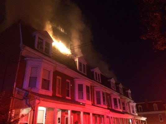 Flames shoot from the third floor of a row home fire on Dallas Street in York City Monday, Nov. 9, 2015.