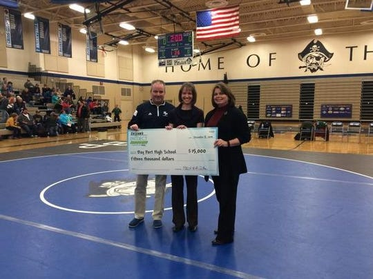 Bay Port High School Principal Mike Frieder, Amy Arbogash from The Giving Tree pantry and Nancy Loberger, account executive for Nsight Telservices, with technology hold the school's check for $15,000 from Cellcom.
