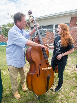 Seventh-grade musician Josie Wise, 14, checks out the upright bass that was donated by Dave Schmidt of Schmidt's Music at Workman Middle School in Pensacola on Wednesday, May 23, 2017. A fire destroyed instruments and sheet music in school's orchestra room on Saturday, May 13, 2017.