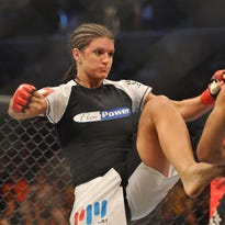 Cris Cyborg (R) battles Gina Carano during their Middleweight Championship fight.