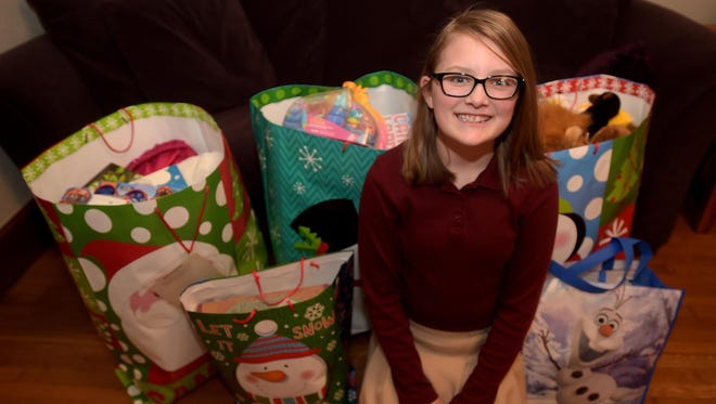 "Olivia Dudas, who created the ""Traveling Bag of Kindness"" to help children in need this Christmas, poses for a photograph Tuesday at her home in Richmond."