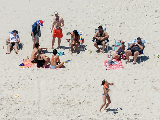 In this July 2 photo, Gov. Chris Christie, right, relaxes