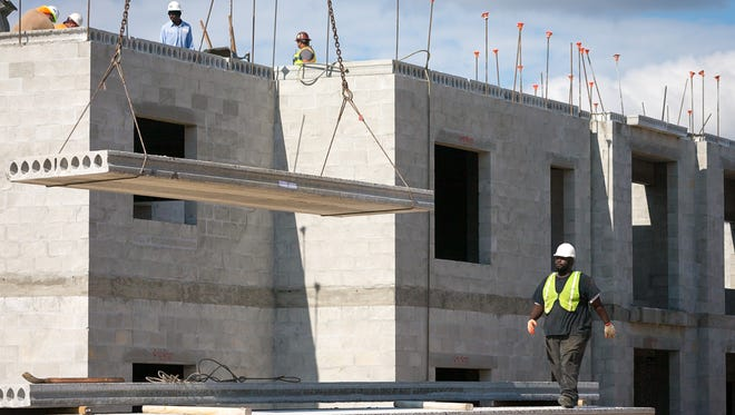 Hollow core planks are lifted into position with a crane during the construction of The Reef student housing complex on Wednesday, Jan. 6, 2016, in Estero. For the year 2015, Lee County issued 1,202 single-family building permits, up 21 percent from 2014. Permits were issued for 2,094 multi-family units in 2015, up 216 percent from the previous year.  (David Albers/Staff)