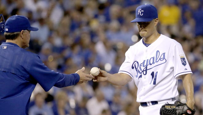 Royals starting pitcher Jeremy Guthrie, right, hands the ball to manager Ned Yost in the third inning Tuesday after Guthrie gave up nine runs to the Seattle Mariners.