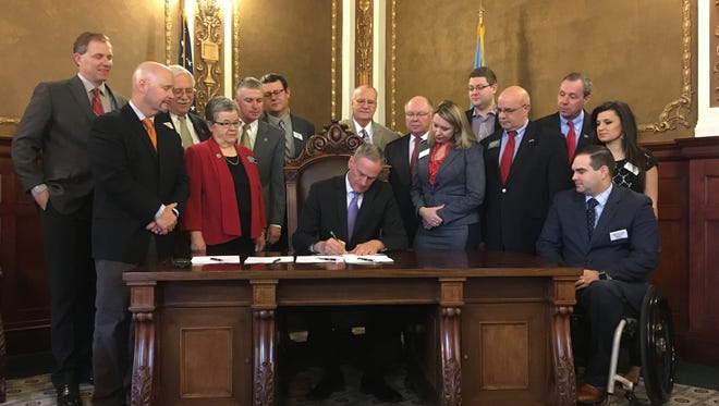 South Dakota Gov. Dennis Daugaard, flanked by state lawmakers, signs ethics reform legislation on March 10, 2107.