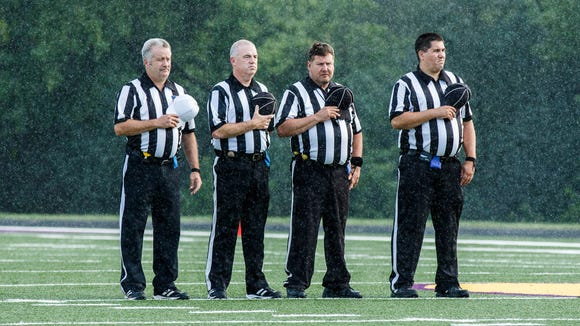 Rain begins to fall during the national anthem at Oconomowoc's season opening football game against Kettle Moraine on Friday, August 19, 2016.