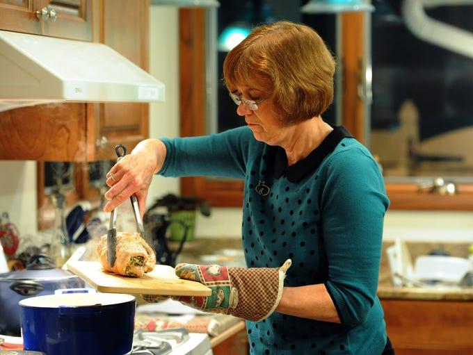 Nancy Stohs readies the main course, stuffed turkey