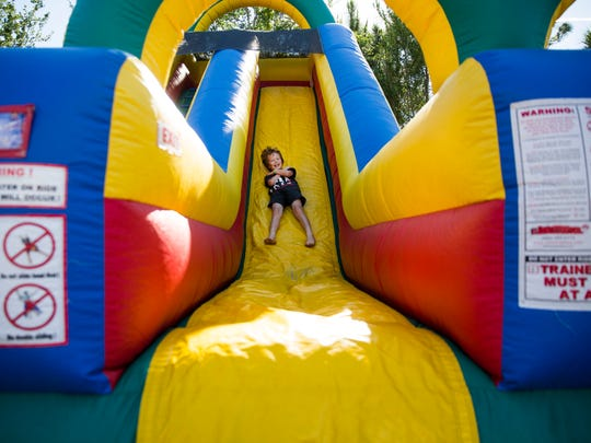 William Harris, 8, laughs as he slides down a bounce slide on Saturday, April 8, 2017 at the inaugural Kidapalooza event at Golisano ChildrenÕs Museum of Naples. Families enjoyed face painting, a bike obstacle course, bounce houses and other hands-on activities.