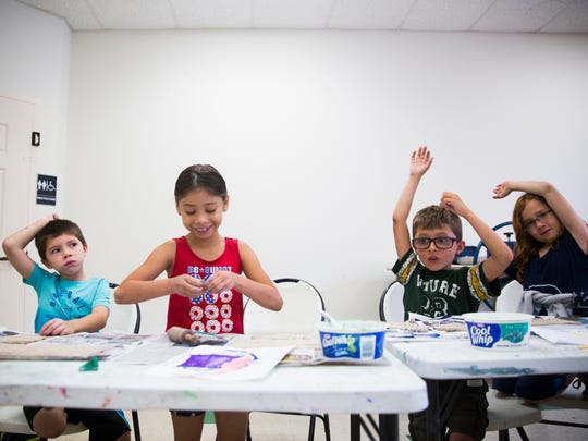 James King, 6, from left, Anale Delgado, 7, Colton Smith, 8, and Dorian Lorch, 8, raise their hands as the teacher asks them to be quiet while making monster cookie jars on Tuesday, June 20, 2017, during summer camp at Center for Performing Arts Bonita Springs.