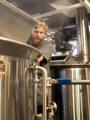 Logan DePover works inside MondoÕs Reunion Brewery Restaurant on Wednesday, Dec. 23, 2015.