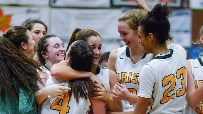 Kate Baufhof, center, is hugged by teammates Gina Citrone (4) Abby Pilkey (3) and Jania Wright (23) after York Catholic defeated Delone Catholic 67-62 on Wednesday, Jan. 4. The Fighting Irish have won 11 of the last 12 District 3 titles, making it a program that would potentially get bumped up in class under the PIAA's latest discussions to improve competitive balance with a new promotion-based system.