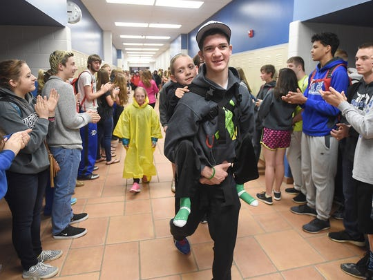 Hunter Gandee, 16, carries his brother Braden Gandee, 9, while students at Dundee High School applauded them as they start off on day two of their Cerebral Palsy Swagger walk to the Capitol on Wednesday, April 20, 2016 in Temperance, Michigan. Hunter expects this will be his last such walk because he will be starting his senior year of high school in the fall and will be preparing for college.