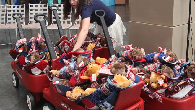 Cadee Caldwell, of Luvybear Quilts 4 Tots, sorts through wagons full stuffed bears after delivering them to Golisano Children's Hospital on Monday.
