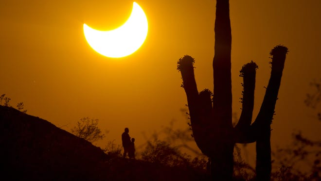Cheryl Evans/The Republic Hikers see a partial solar eclipse over Phoenix in 2012. Another partial eclipse will be visible from Arizona today starting at 2:21 p.m. Some people in Papago Park in Phoenix get a sublime glimpse Sunday of the partial solar eclipse in which the moon's silhouette nipped out a big chunk of the sun's surface area. Cheryl Evans/The Republic 0520120830 PNI0520-eclipse 5/20/12   Hikers view a partial solar  eclipse in Papago Park in which the moon's silhouette blocked 83 percent of the suns's surface area in Phoenix. Cheryl Evans/The Arizona Republic