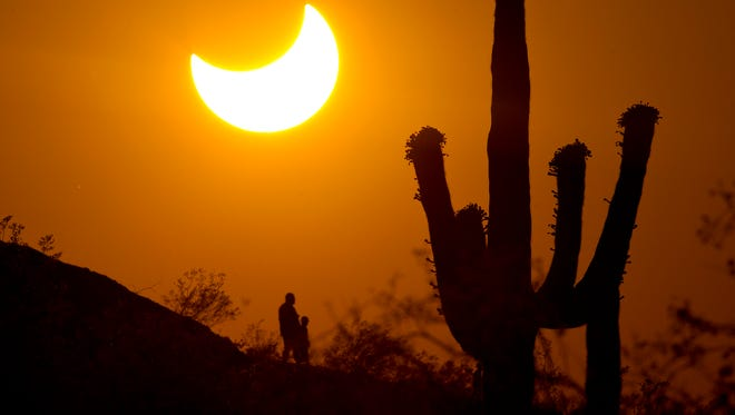 Hikers view a partial solar  eclipse in Papago Park in Phoenix in 2012.