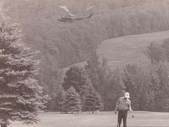 A golfer plays on while an Army Air National Guard helicopter aides in the search for Thompson in 1987.