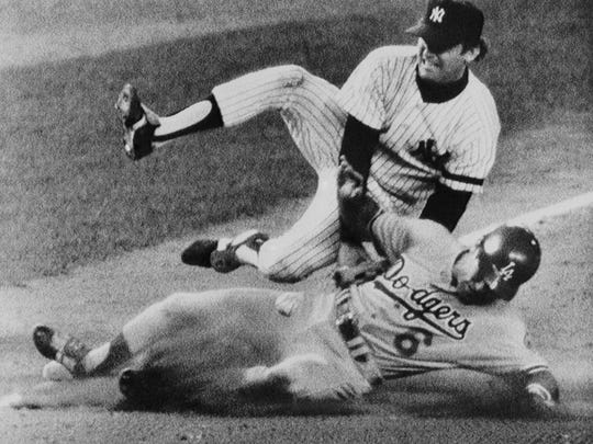 FILE - In this Oct. 21, 1981 file photo, Los Angeles Dodgers runner Steve Garvey goes into third base safely as New York Yankees third baseman Graig Nettles drops the ball in the fifth inning of  the World Series game in New York. It's been 33 years since teams from these cities played for a title. The rivalry could be lost on many fans when the Kings and Rangers meet for the Stanley Cup. (AP Photo/File)