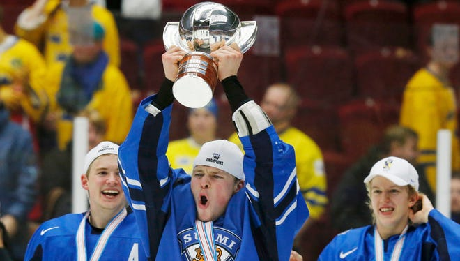 Finland's Mikko Lehtonen celebrates with the trophy after his team defeated Sweden in overtime of their World Junior Championships gold medal game.