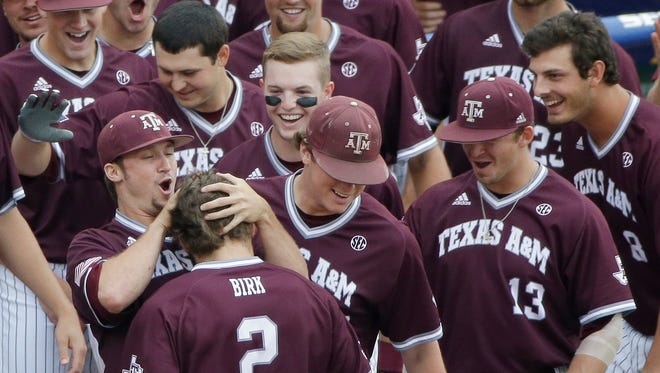 Texas A&M Ryne Birk is greeted by his teammates after hitting a home run during the second inning.
