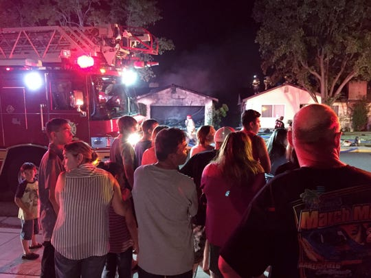 Neighbors watch as firefighters battle a house fire Saturday night in the 2200 block of South Terrace Street in Visalia