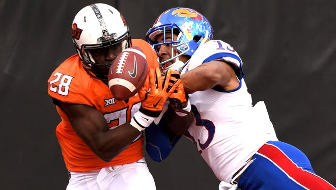 Kansas corner back Hasan Defense, right, and Oklahoma State wide receiver James Washington struggle for control of an incomplete pass during the first half of an NCAA college football game in Stillwater, Okla., Saturday, Nov. 25, 2017.
