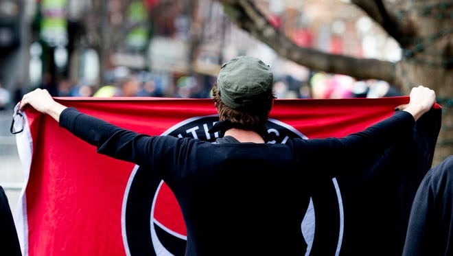 An Antifa member waves their flag during the second annual Knoxville Women's March in Knoxville, Tennessee on Sunday, January 21, 2018. Around 20 members of the white nationalist group Traditionalist Worker's Party made an appearance as well as Antifa protestors.