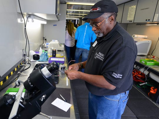 Optometrist Edward Mitchell, Jr. makes a new pair of glasses Saturday at the Remote Area Medical clinic at Milton High School. Patients received free medical, dental and vision services as well as free hair cuts.