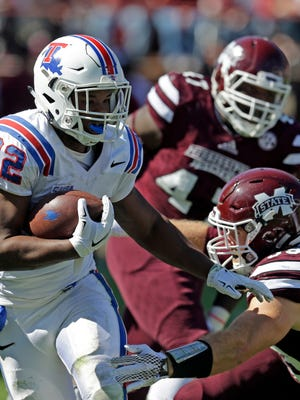 Running back Jarred Craft  (22) of the Louisiana Tech Bulldogs tries to get past linebacker Richie Brown (39) of the Mississippi State Bulldogs as he carries the ball during the second quarter of an NCAA college football game at Davis Wade Stadium last season.