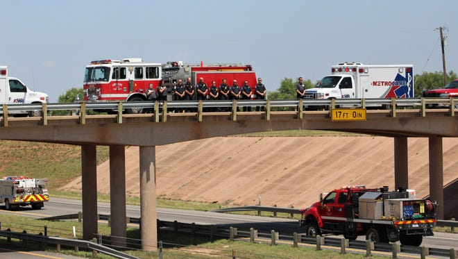 Abilene Fire Department and MetroCare ambulance personnel line the Hayter Road bridge over Interstate 20 on Monday afternoon to pay their respects to fallen Weatherford firefighter Richard Loller, who died while deployed to a wildland fire in the Davis Mountains last weekend.