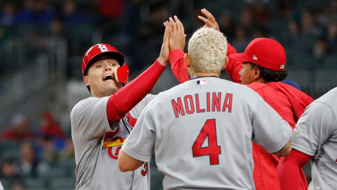 St. Louis Cardinals' Aledmys Diaz, left, celebrates at the dugout entrance after scoring on a two-run homer by Tommy Pham in the third inning of a baseball game against the Atlanta Braves Friday, May 5, 2017, in Atlanta. (AP Photo/John Bazemore)