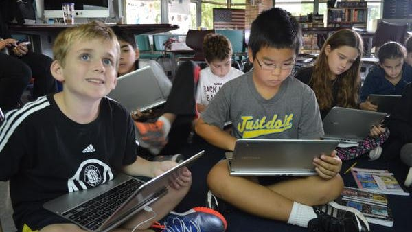 At Heathcote School in Scarsdale, fifth grader David Appel, left, looks up at the Smartboard screen while classmate Ken Zhu does research on a Chromebook computer.