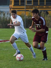 Arlington's Michael Vanikiotis, right, takes the ball down field as Ketcham's Mitchell Kuehner, left, defends during Monday's game.