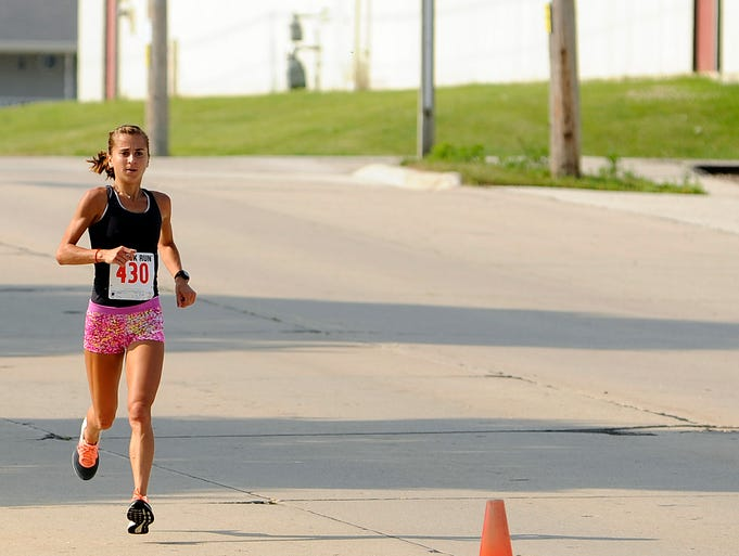 Kelly Greenwood of Two Rivers heads for the final stretch in the 6th annual Ron Rubick Run on Saturday, Aug. 1, 2014 at Ron Rubick Municipal Field in Manitowoc. The 5k (3.1mi) race started at Manitowoc Lincoln High School at 9 am and benefits Manitowoc Lincoln High School, Holy Family Hospital Cancer Center, and Aurora Medical Center - Two Rivers. Greenwood placed first overall in the run. Matthew Apgar/HTR Media