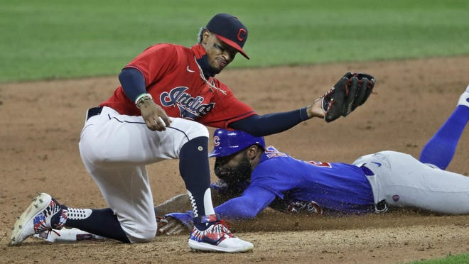 Chicago Cubs' Jason Heyward, right, steals to second base as Cleveland Indians' Francisco Lindor lets the ball get by him in the eighth inning in a baseball game, Wednesday, Aug. 12, 2020, in Cleveland.