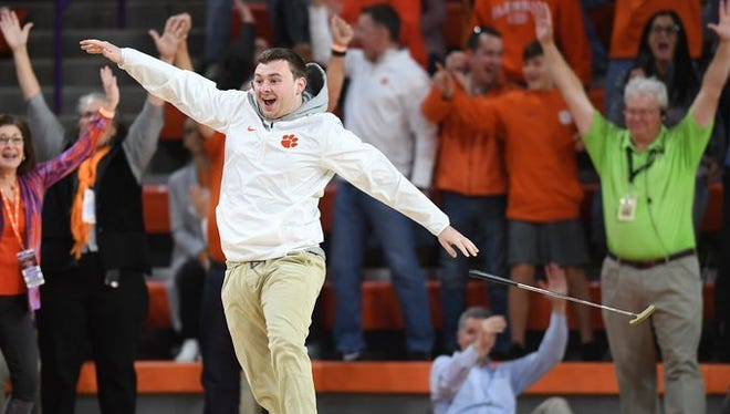 Clemson student Chris Carns reacts after sinking a 94-foot putt for $10,000 Saturday afternoon during a break between Clemson's basketball game against Louisville in Littlejohn Coliseum.