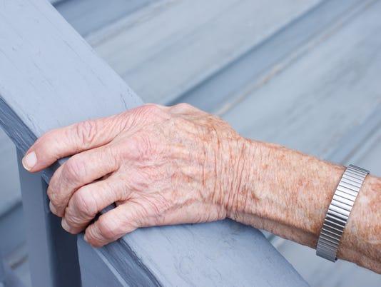 Senior lady holding stair rail