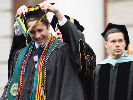Chris Petrillo receives an award from UVM President Tom Sullivan during the University of Vermont graduation ceremony on Sunday morning May 20, 2018 in Burlington.