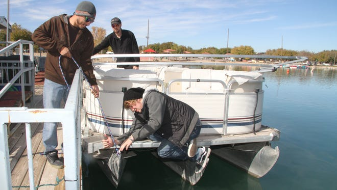 Jay Balzano perches on the back of the Bella Notte, as Nico Barrera and T.J. Ryan look on. Balzano, Barrera and Ryan will be captaining the boat and its larger sister boat, the Bella Sera, for guests enjoying Christmas on the Pecos.