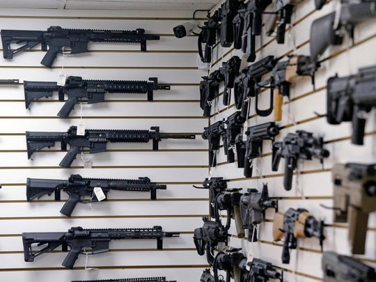 Dozens of semi-automatic rifles line a pair of walls in a gun shop Nov. 7, 2017, in Lynnwood, Wash.