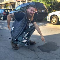 Jeff Salazar and Jonathan Weir, (right) both of Hamtramck stand on Lumpkin St. near the potholes that need to be repaired on Monday, July 27, j2015.