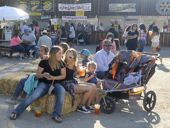 A crowd of fair-goers relax near the concession stands.