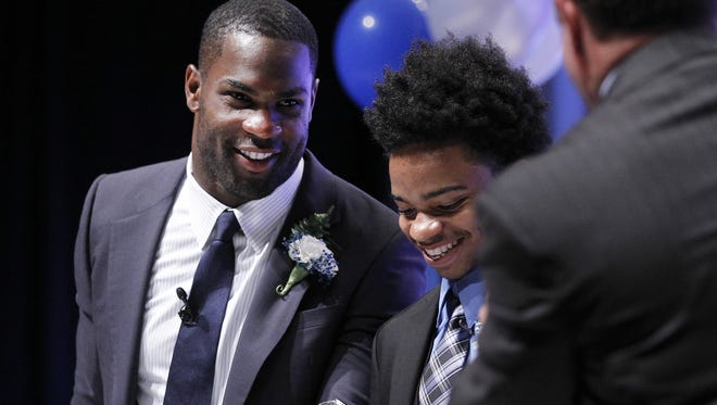 DeMarco Murray, Rochester Press-Radio Club Sports Personality of the Year, left, poses with Honorary Chairperson Rimeek Washington, right, as he is presented with a Dallas Cowboys helmet signed by Murray.